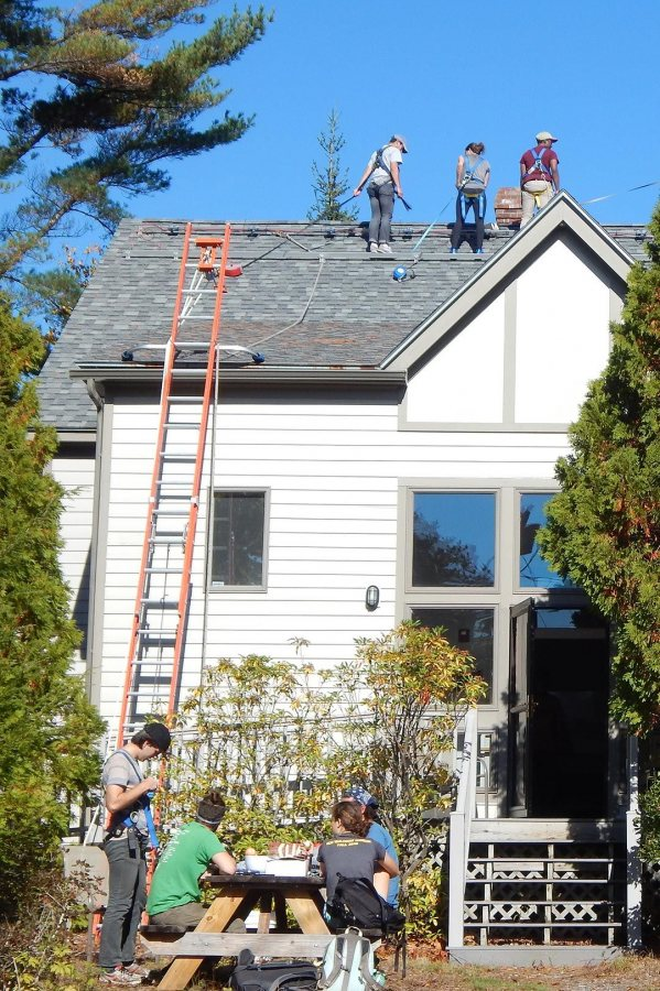 With student teams high and low, preparation for the installation of solar photovoltaic panels on Bates' Coastal Research Center, aka Shortridge, is underway late in the morning of Oct. 19, 2016. (Doug Hubley/Bates College)
