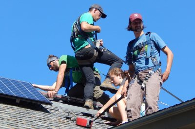 A PV panel installation squad: from left, George Fiske '19, Aston Ireland of ReVision Energy, Katharine Gaillard '19, sustainability manager Tom Twist. (Doug Hubley/Bates College)