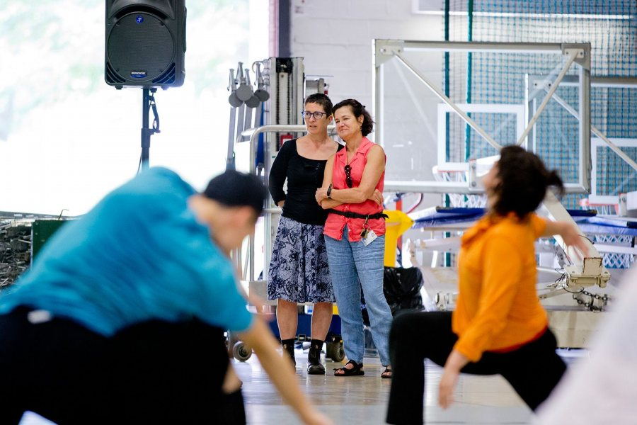 Professor of Dance Carol Dilley, left, and Bates Dance Festival Director Laura Faure observe the last minutes of a three-week modern dance class taught in 2015 by Omar Carrum in the Gray Athletic Building. (Phyllis Graber Jensen/Bates College)