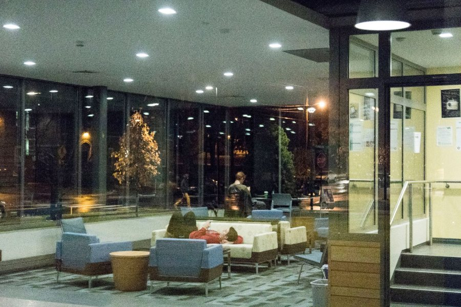 An evening scene in the lobby of Chu Hall is reflected in the building's storefront glass. A mix of furniture, an inventive floor plan, and an attractive fireplace around the corner make the lobby an attractive gathering spot. (Josh Kuckens/Bates College)