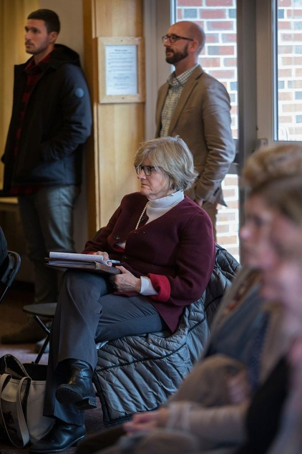 "Bates President Clayton Spencer takes notes in the Mays Center during the ""What Just Happened?"" panel analyzing the 2016 election. Standing behind Spencer are Writing Specialist Chris Petrella, at left, and Dean of Students Josh McIntosh. (Phyllis Graber Jensen/Bates College)"