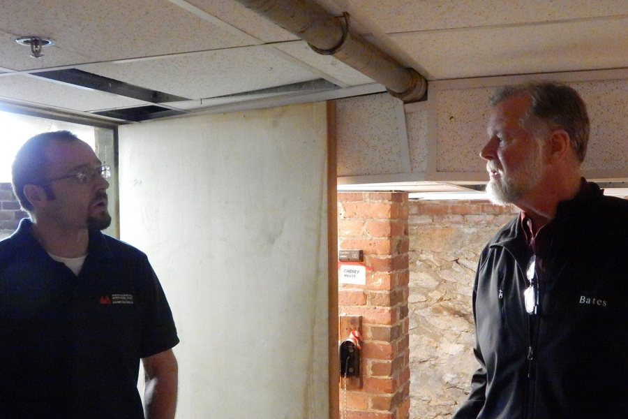 Aaron MacFawn of Maine Controls, at left, confers with Bates energy manager John Rasmussen in the basement of Cheney House after the installation of remote heating controls and sensors on Nov. 15. (Doug Hubley/Bates College)