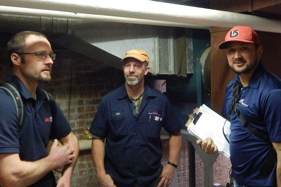 Technicians pose for Campus Construction Update after completing the installation of remote heating controls at Libbey Forum on Nov. 16, 2016: from left, Aaron MacFawn of Maine Controls; John Begin of Damon Mechanical; and Mike Renk of JM Electrical. (Doug Hubley/Bates College)