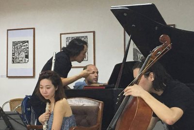 "Hiroya Miura consults with Third Sound pianist Orion Weiss as four members of the ensemble rehearse Miura's ""Open Passage"" in Havana. Also shown are flutist Sooyun Kim and cellist Michael Nicolas; out of the frame is violinist Adda Kridler. (Courtesy of Hiroya Miura)"