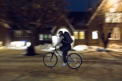 Hadley Moreau '19 of Falmouth, Maine cycles across campus on a Den Delivery run.