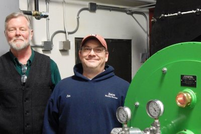 Bates energy manager John Rasmussen, at left, and boiler operator John Jasper pose by the new Renewable Fuel Oil burner on Jan. 19, 2017. (Doug Hubley/Bates College)
