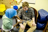 "Bill Curley '16 of Wilton, Conn., works with a participant in a session of the ""How Everything Works"" program at the Hillview Community Resource Center. Held in February 2016, the session explored first aid practices. (Phyllis Graber Jensen/BAtes College)"