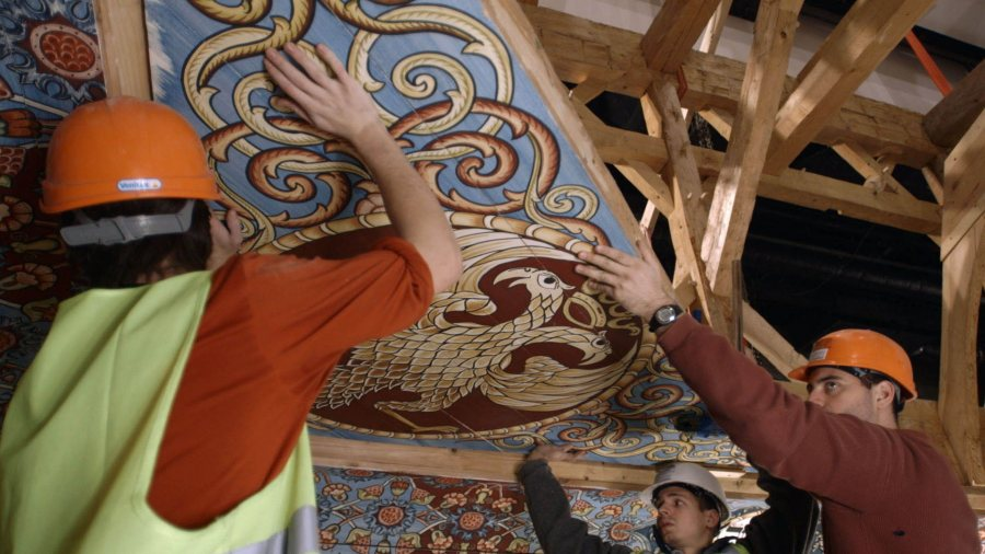 "A construction crew places a painted ceiling panel into place in this scene from ""Raise the Roof,"" a film about the reconstruction of a wooden 18th-century Polish wooden synagogue. (Trillium Studios)"