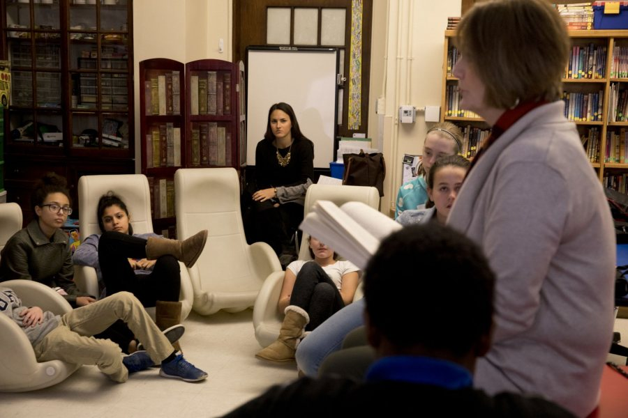 Elizabeth Erbafina '17, center, listens as Sue Weber '74 reads to a seventh-grade literacy class at Lewiston Middle School on March 2. Erbafina is student-teaching with Weber. (Phyllis Graber Jensen/Bates College)