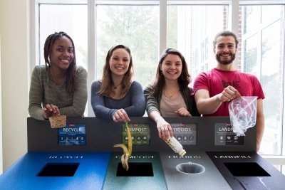 Four Bates EcoReps -- Isa Moise '19 of Mount Vernon, N.Y., Beanie O'Shea '18 of Somers, Conn., Hannah Slattery '18 of Gilford, N.H., and George Fiske '19 of West Hartford, Conn. -- show off one of the college's new waste-sorting stations, in Pettengill Hall. (Josh Kuckens/Bates College)