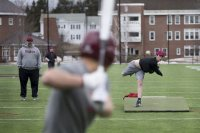 As head coach Jon Martin watches, Miles Michaud '20 delivers a pitch during baseball practice on Garcelon Field, the team's home away from home until Leahey Field is ready. (Phyllis Graber Jensen/Bates College)