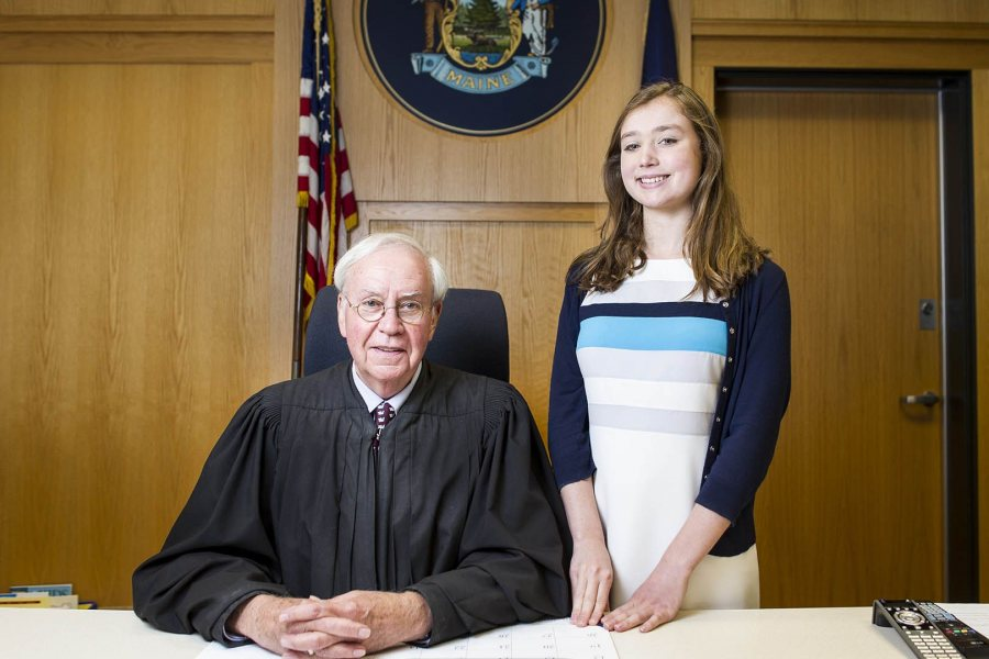In August 2015, Claire Brown '17 poses with Judge John Beliveau at the Maine District Court in Lewiston. Her judicial internship, which inspired her honors thesis research on adult drug court effectiveness, was funded in 2015 and 2014 by the college's Harward Center for Community Partnerships. (Josh Kuckens/Bates College)