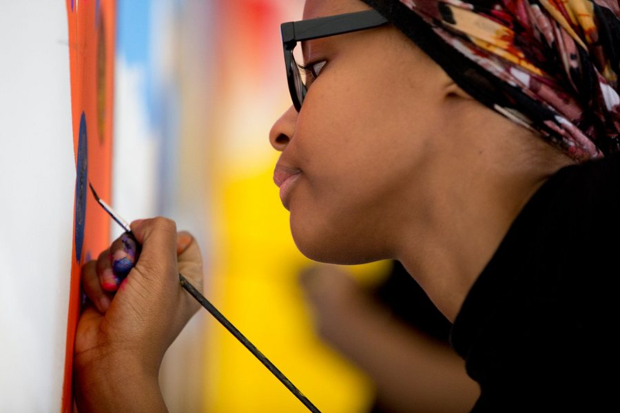 An unidentified Lewiston High School student, a member of the 21 Century Leaders program, does detail work on the YWCA mural. (Phyllis Graber Jensen/Bates College)