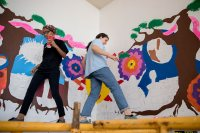 With the mural taking shape behind them, an unidentified Lewiston High School student, left, and Eden Rickolt '20 choose their steps carefully on the scaffold. (Phyllis Graber Jensen/Bates College)