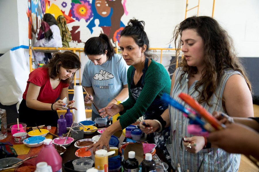 "From left, Daisy Diamond '19, Eden Rickolt '20, Carolina Gonzalez Valencia, a lecturer in art and visual culture, and Dani Klein '17 mix colors for the ""Women of Color Leading Change"" mural. Phyllis Graber Jensen/Bates College)"