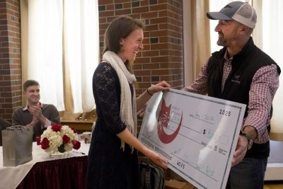 Bobcat Venture Pitch Competition judge Chris Barbin '93 gives first-place winner Ali Rabideau '17 of Natick, Mass., a $9,000 check for her pitch, Herban Works, a line of home products made from medicinal herbs and flowers by at-risk women of the Center for Wisdom's Women in Lewiston. (Phyllis Graber Jensen/Bates College)