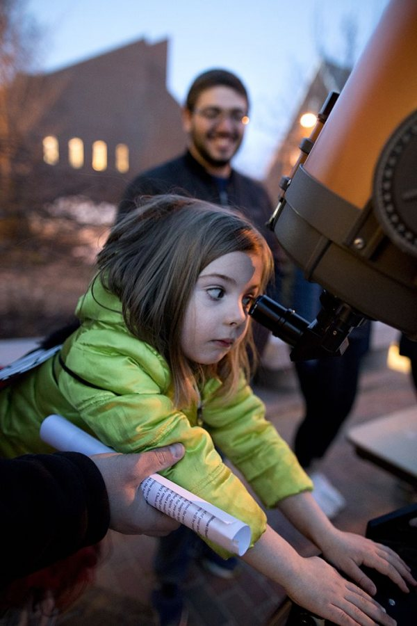 Isla Shea, 6, of East Auburn School, uses a telescope to view the moon as Evan Goldberg '19 looks on during the Astronomy Extravaganza on April 3. (Phyllis Graber Jensen/Bates College)