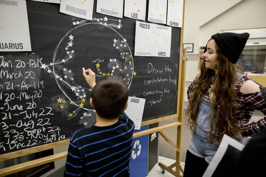 A boy works on the Connect the Constellations display as Emily Morse '17 of Machias, Maine, watches in Memorial Commons in Chase Hall. (Phyllis Graber Jensen/Bates College)