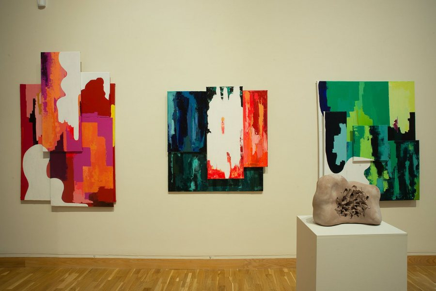 Three untitled paintings by Joanie Oates, with a sculpture by José Herrera in the foreground.