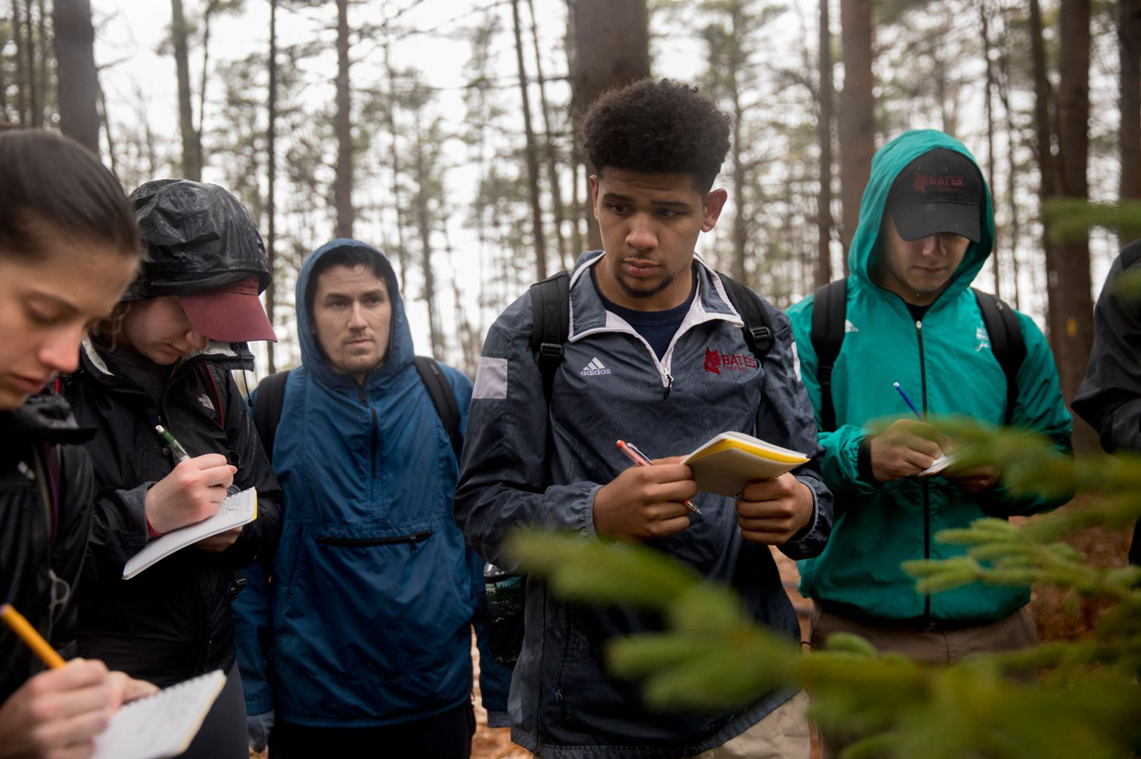 "Short Term supports off- campus in locations far and near. Here, Sara Buscher '19, Karly Oettgen '19, Tyler Sorkin '18, Marcus Ross '19, and Bobby Dee '19 make notes about red spruce trees during a Short Term field trip to the Saco Heath Preserve in Saco, Maine. Assistant Professor of Biology Brett Huggett leads the course ""North Woods"" that brought the group to the preserve. (Phyllis Graber Jensen/Bates College)"