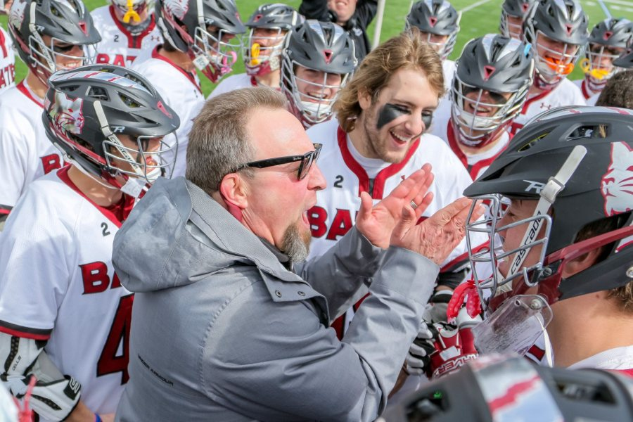 Head coach Peter Lasagna and the men's lacrosse team celebrate after defeating Middlebury at Garcelon Field. The win put Bates at 10-0. (Brewster Burns for Bates College)