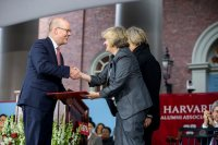 Phillip Lovejoy, executive director of the Harvard Alumni Association, presents Bates President Clayton Spencer with the association's Harvard Medal on May 25. Behind Spencer is Harvard president Drew Faust. The HAA's annual meeting took place in Tercentenary Theatre, Harvard, during the afternoon program of Harvard's Commencement. (Rose Lincoln/Harvard University)