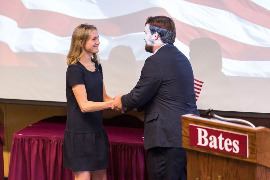"Molly Chisholm '17, playing a fictional Republican governor of Massachusetts, shakes hands with her mock-election opponent Gabriel Nott '17 during a debate held as part of the 2017 ""Presidential Campaign Rhetoric."" (Josh Kuckens/Bates College)"