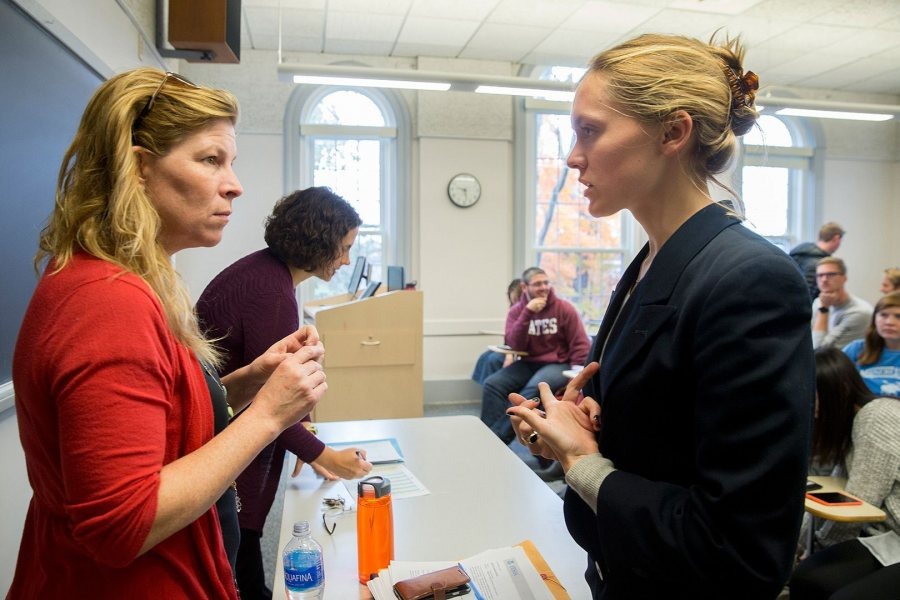 "Associate Professor of Rhetoric Stephanie Kelly-Romano, at left, confers with Molly Chisholm during the fall 2017 course ""Presidential Campaign Rhetoric."" As Chisholm has honed the Senior Address she'll be giving May 28 at Commencement, Kelley-Romano has been a valued adviser. (Phyllis Graber Jensen/Bates College)"