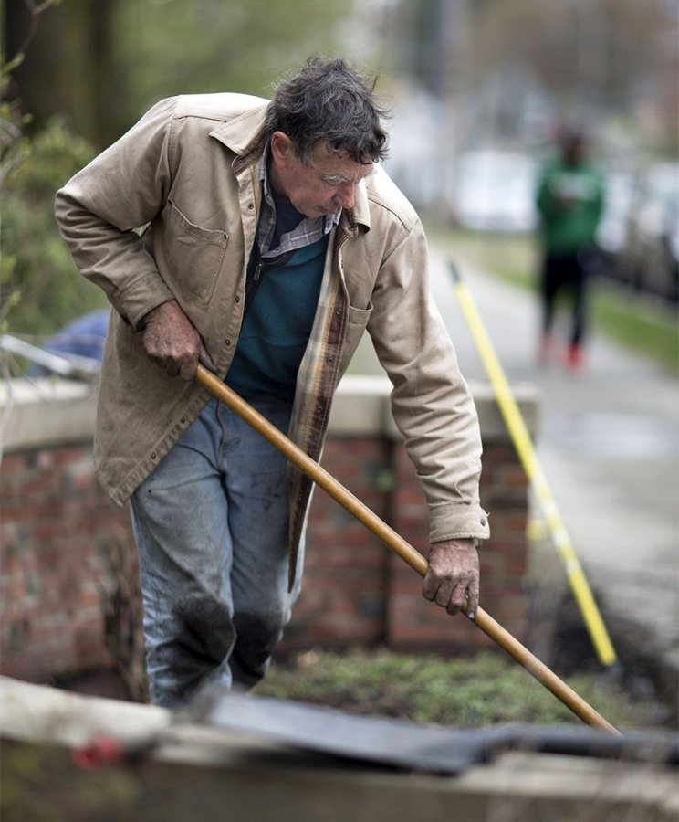 Bill Bergevin sweeps the sidewalk after a mulching session near Carnegie Science Hall. (Phyllis Graber Jensen/Bates College)