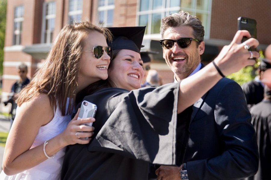"Kate Berger '17 (center) and classmate Sadie James take a selfie with actor and Bates honorand Patrick Dempsey as graduates line up on Alumni Walk. Berger, whose twin sister heard a former vice president speak at Colby College's graduation last week, commented, ""This beats Joe Biden."" (Phyllis Graber"