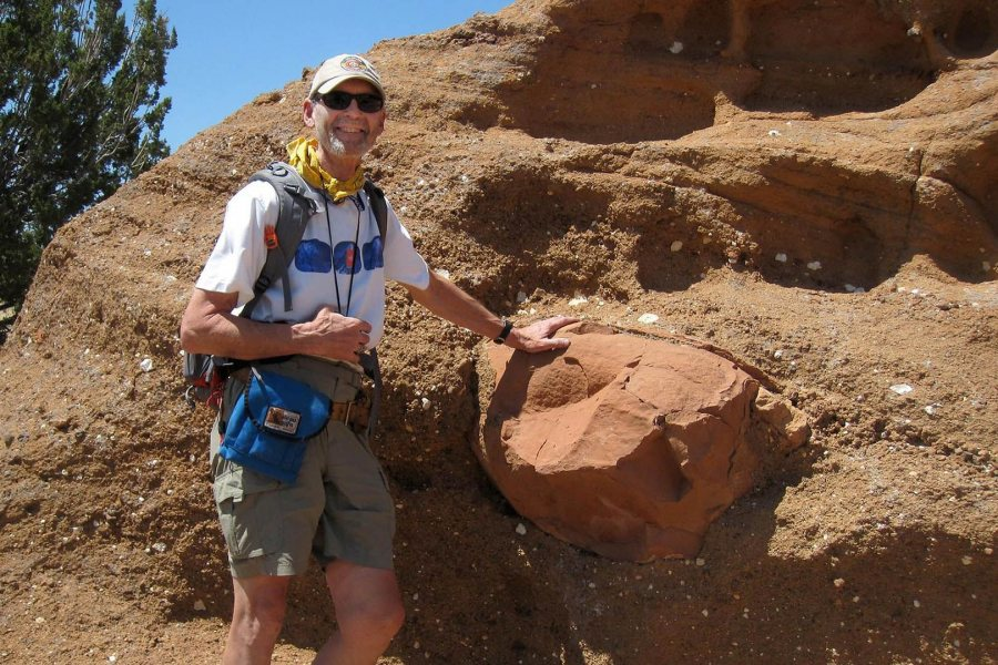 "Near Flagstaff, Arizona, in 2011, on his final Short Term trip to the U.S. Southwest, John Creasy poses next to examples of ""volcaniclastic"" rock that's been moved or affected by wind, water, or similar action. (Photograph by Dykstra Eusden '80)"