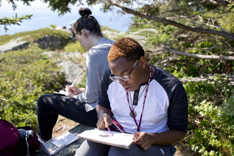 """In 2015, Mickai Mercer '19 of Philadelphia and a fellow first-year sit and sketch during their AESOP trip to the art colony on Monhegan Island. This year's Monhegan trip is """"Art/Meditation"""" with: Olga Revzina '18 of Bethesda, Md., and John Ricatto '18 of Ridgewood, N.J. (Phyllis Graber Jensen/Bates College)"""