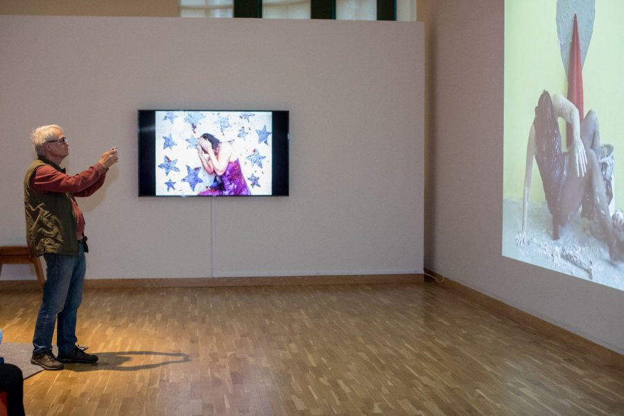 A visitor to the Bates Museum of Art takes in videos by, and showing, performance artist Kate Gilmore '97. Gilmore takes part in a Sept. 27 panel on performance art in conjunction with her exhibition In Your Way. (Rene Roy for Bates College)