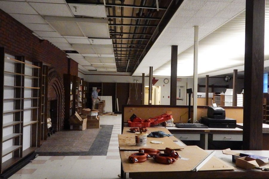 The black pipes at top center will carry water from the Chase Hall mechanical room to fan-coil units that will heat and cool the Den and Memorial Commons. Project manager John Rasmussen is standing by the fiction section of Bates' former bookstore. (Doug Hubley/Bates College)