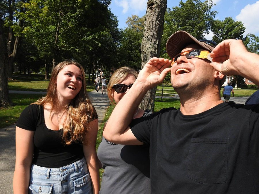 Pete Culcasi of Northbridge, Mass., looks at the eclipse through protective eyeglasses as his daughter, Maddie, and wife Jody, watch. A welder by trade, he'd also brought protective welder's glass. (Jay Burns/Bates College)