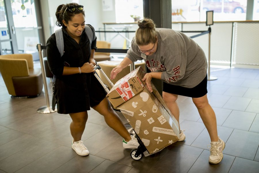 Retail Shipping and Parcel Clerk Laurie Grimmel helps Elizah Laurenceau '19 load recently-delivered packages onto a hand dolly on Oct. 10. (Phyllis Graber Jensen/Bates College)