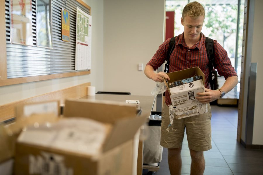 Joe Inger '21 opens a new pair of earbuds in Post & Print on Oct. 10. (Phyllis Graber Jensen/Bates College)