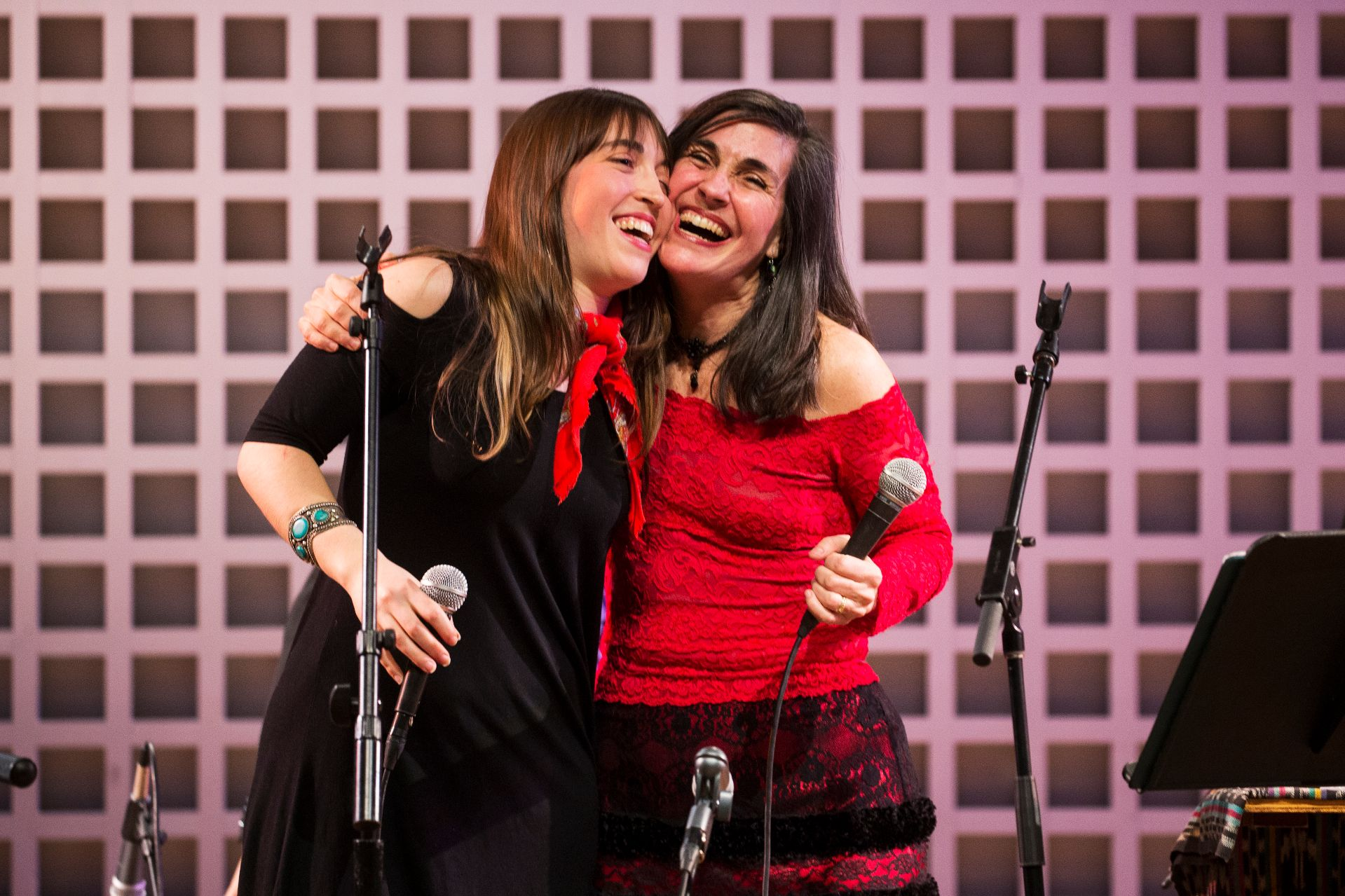 Alisa Amador '18 of Cambridge, Mass., and her mother, Rosi Amador, embrace during a performance by the group Sol y Canto, whose principals are Alisa's parents, Rosi and Brian. Alisa joined them for the Olin Concert Series event. (Theophil Syslo/Bates College)