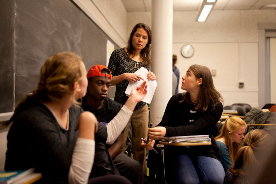 Assistant Professor of Education Mara Tieken circulates among small groups of students as they discuss what makes good teaching. Through fieldwork and classroom work, education students learn about the field's interdisciplinary perspectives and the practical realities today.