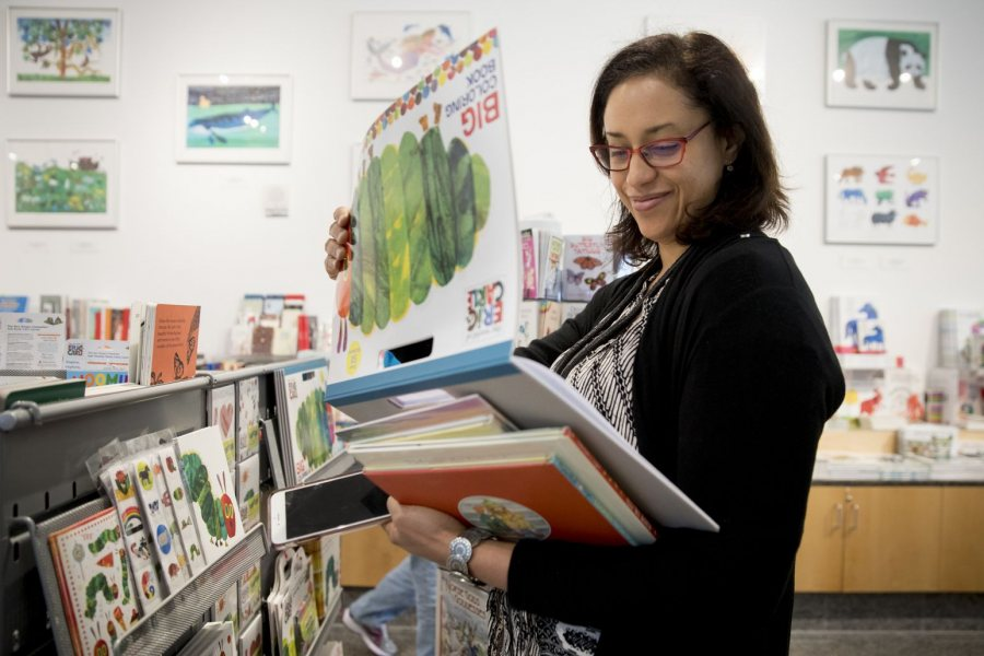 Professor of Psychology Krista Aronson looks at picture books during a trip to the Eric Carle Museum of Picture Book Art in Amherst, Mass., in 2017. Aronson is the creator of Diverse BookFinder, a first-of-its-kind database for identifying and exploring multicultural picture books. (Phyllis Graber Jensen/Bates College)
