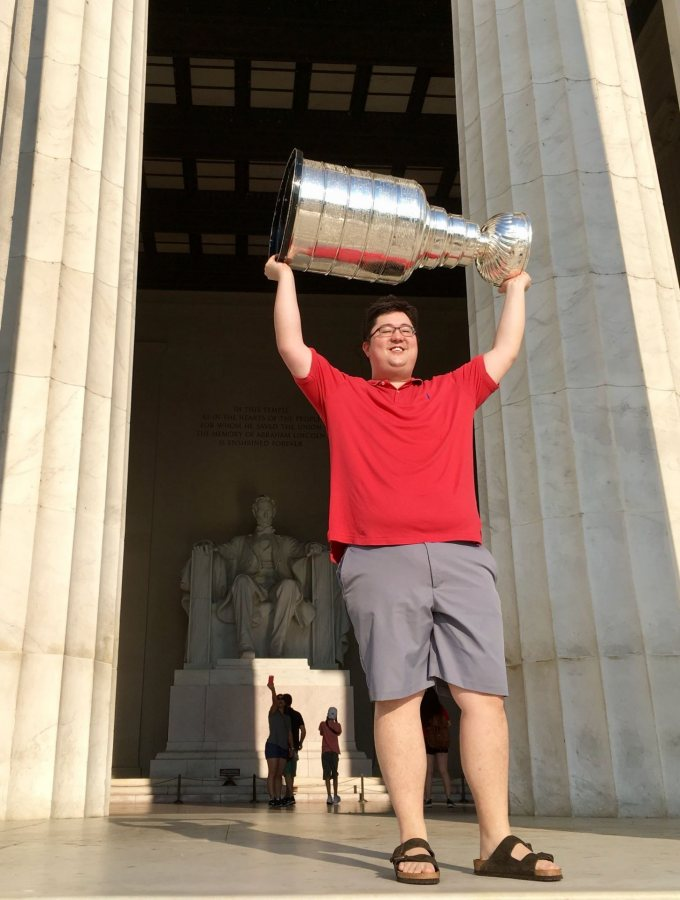 Tim Ohashi '11, a member of the NHL championship Washington Capitals coaching staff, hoists the Stanley Cup at the Lincoln Memorial on the morning of July 3, 2018. (Photograph by Walt Neubrand / Hockey Hall of Fame)