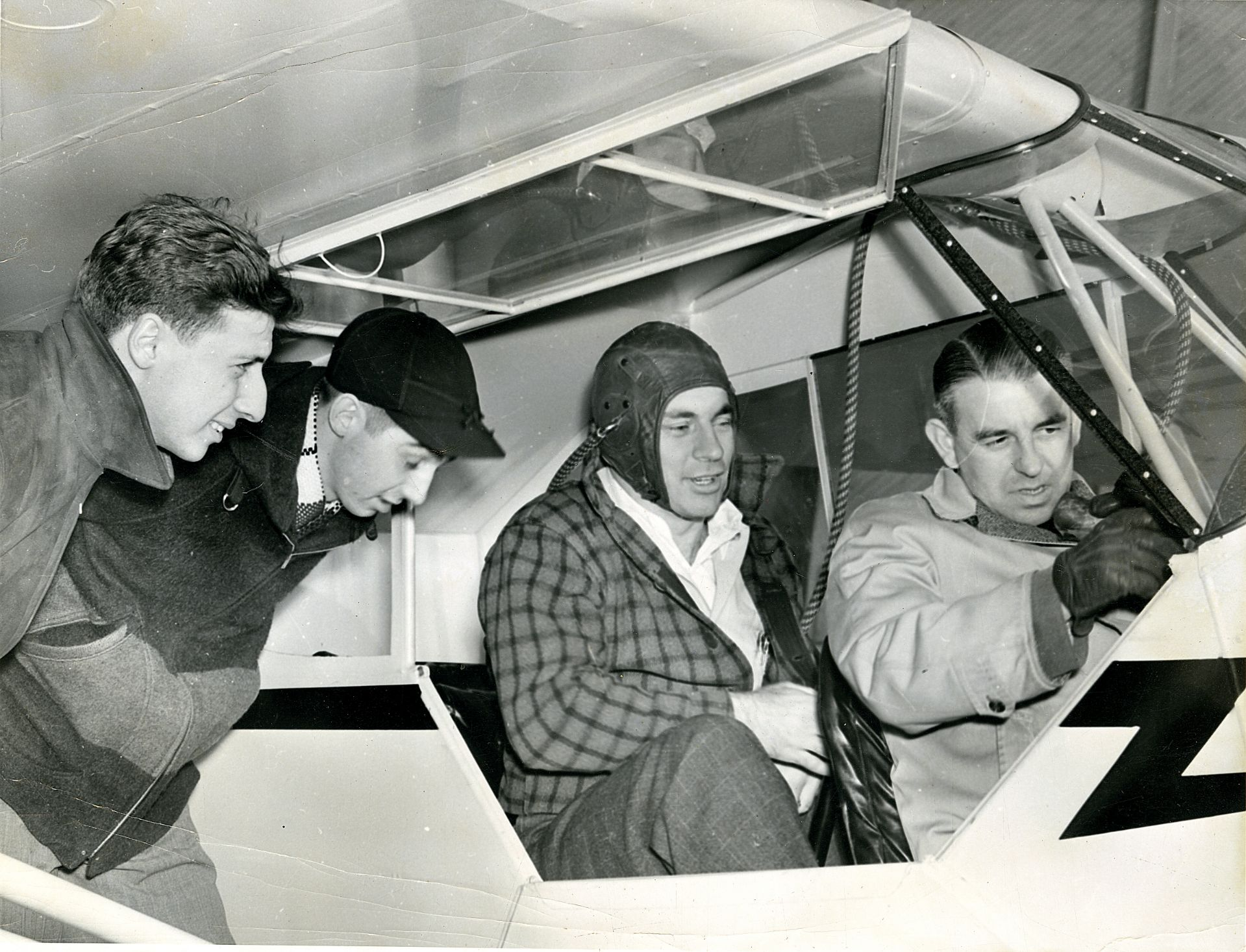 From left, Armand Daddazio '42 (left) Raymond Harvey '42, John Daikus '40 listen to flight instructor Randy Mulherin (right) during flight training on Nov. 25, 1939.