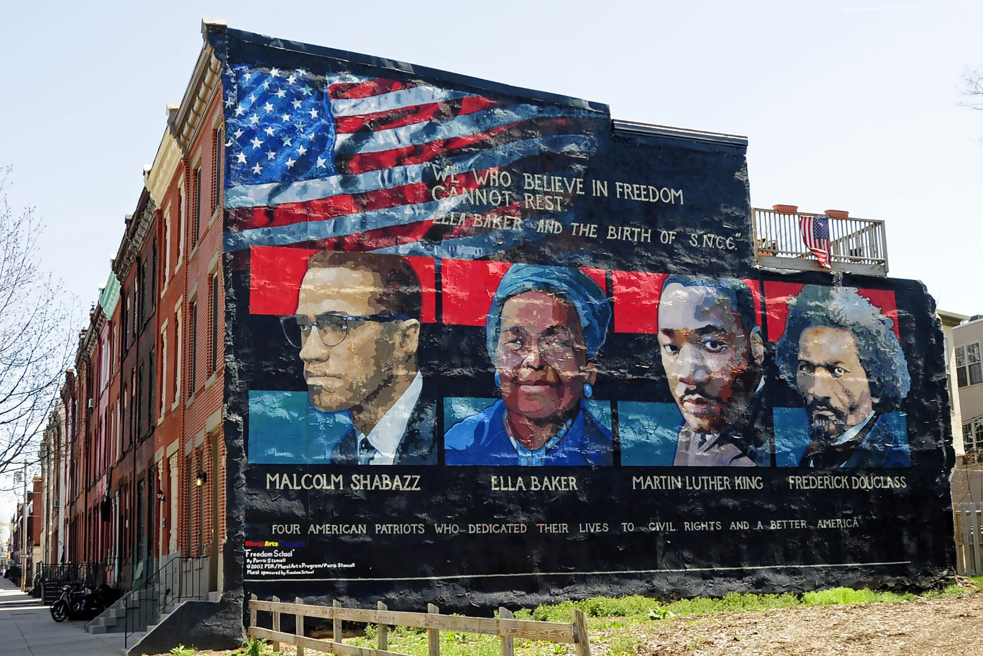 """A mural on the wall of row houses in Philadelphia depicts, from left, Malcolm X, Ella Baker, Martin Luther King Jr., and Frederick Douglass. The quote, """"We who believe in freedom cannot rest,"""" is from Ella Baker. The mural artist is Parris Stancell. (Tony Fischer [CC BY 2.0 https://creativecommons.org/licenses/by/2.)], via Wikimedia Commons)"""