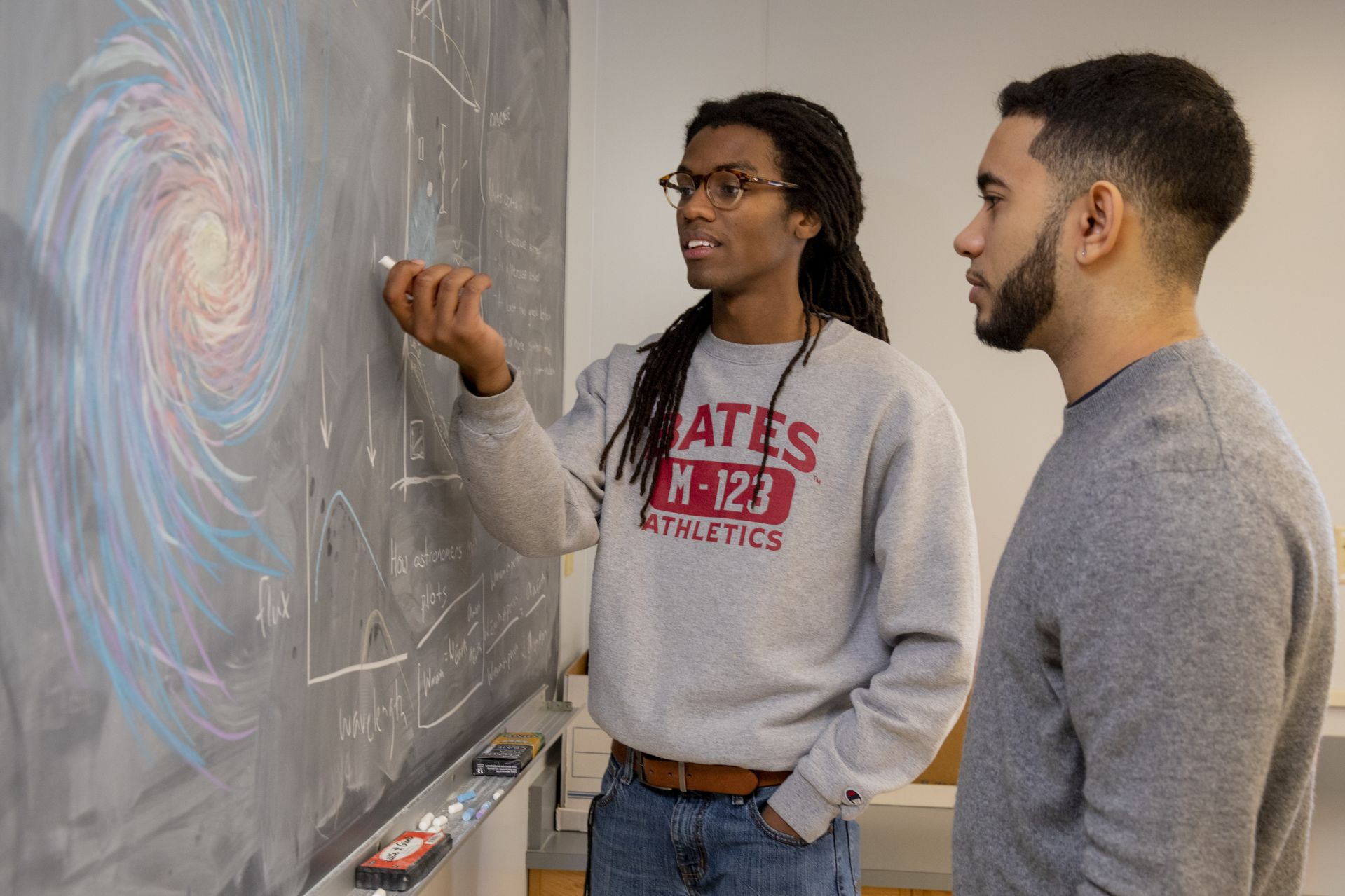 Physics students Kingdell S. Valdez '19 of Andover, Mass. (gray sweater) and Cristopher Thompson '19 of Macon, Ga., (Bates track sweatshirt) pose for photographs and discuss a physics problem at the blackboard in third-floor Carnegie Science physics lab on March 7, 2019.They are working on a collaborative physics senior project, doing different aspects w/similar data, turning in separate documents.