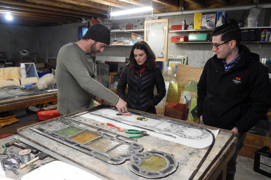 Stained-glass maker Nat Croteau of Phoenix Studio, at left, explains a point of technique to project managers Shelby Burgau of Bates and Dylan Poulin of Consigli Construction. (Doug Hubley/Bates College)