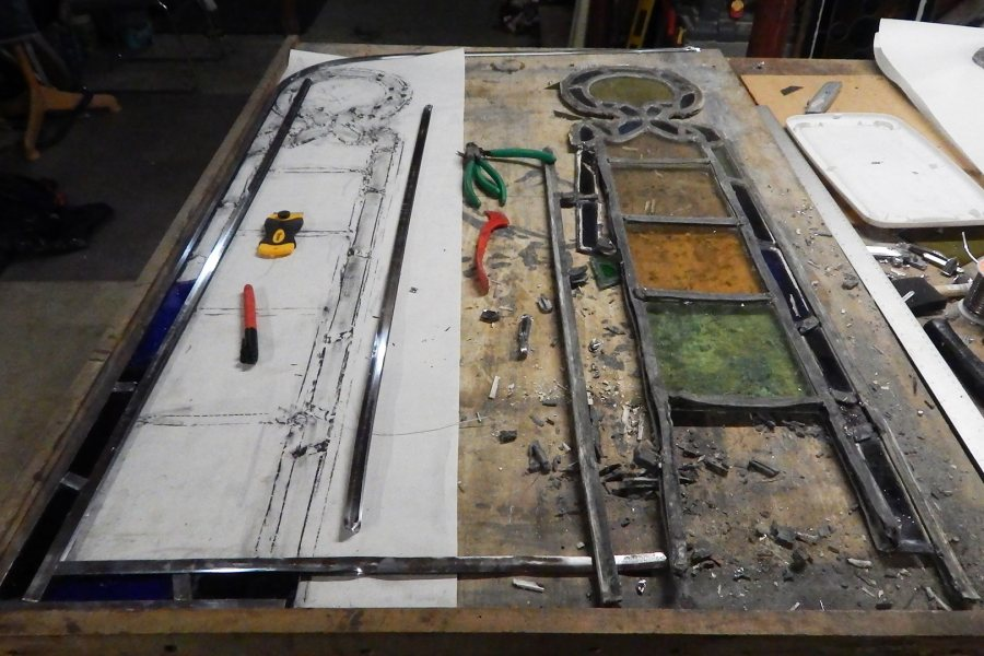 A partially dismantled stained-glass door insert at right, with materials for rebuilding it laid out at left. (Doug Hubley/Bates College)