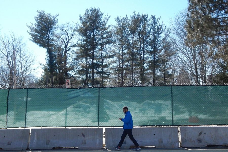 A student passes the newly fenced-in site of Bates' future science building on March 19, 2019. (Doug Hubley/Bates College)