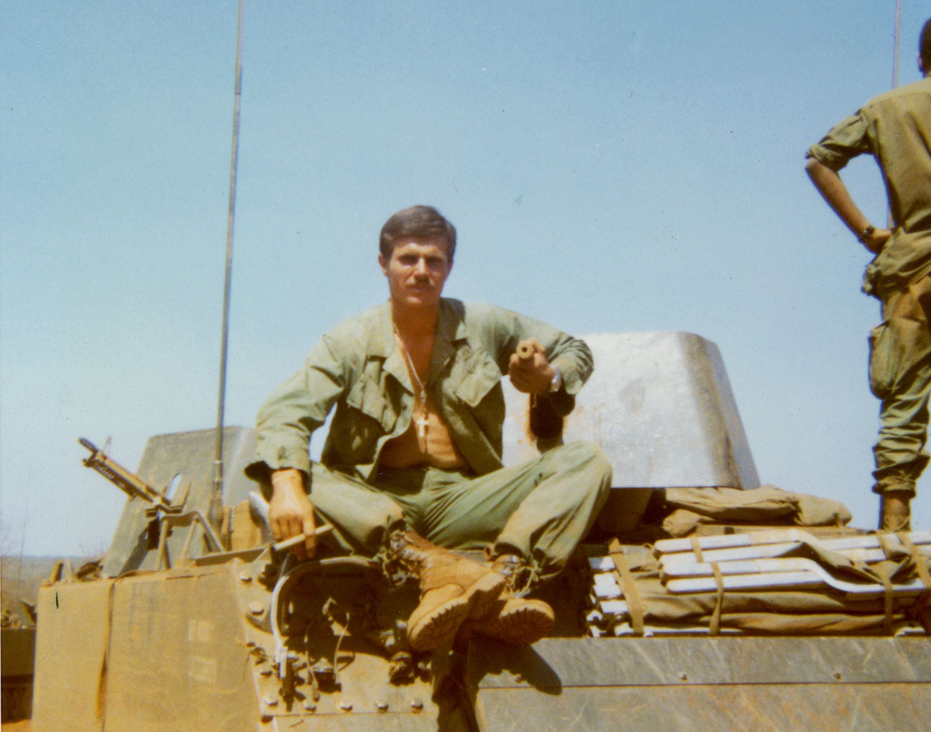 "David Nash '68 sits atop his armored cavalry assault vehicle, or ACAV, in Vietnam in January 1970. He wrote on the back that ""have to do something about that beer belly."" (Courtesy of Susan Rice)"
