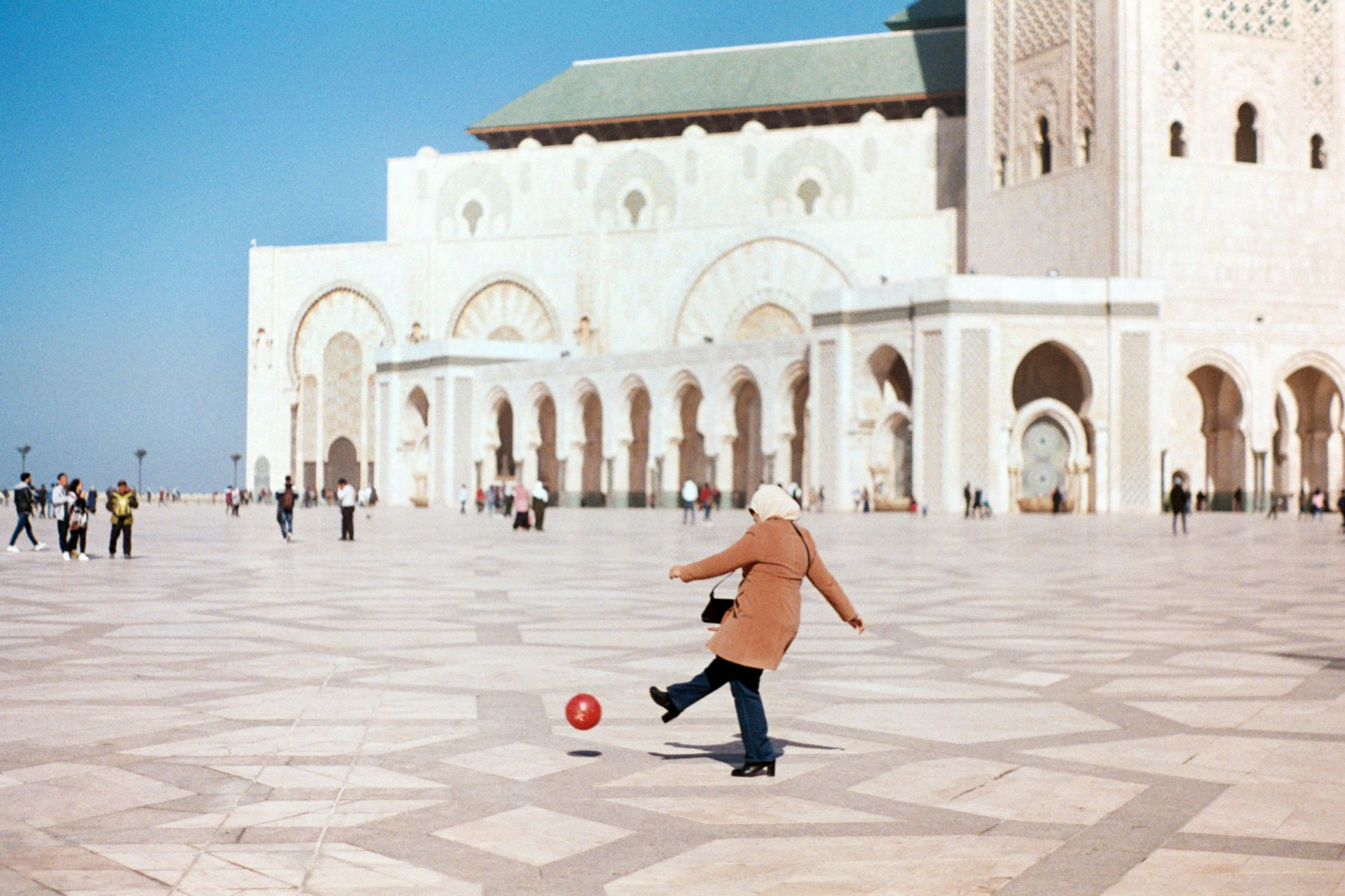 Klein, Josh SIT Morocco Spring 2018 A mother plays soccer with her son outside of the Hassan II Mosque in Casablanca, Morocco. Crowds of people gathered in the expansive square after leaving the International Book Fair that takes place in the capital every February. The mosque is the largest on the continent of Africa and was built overlooking the Atlantic Ocean to commemorate the late King. This photo was selected for the 2019 Barlow Off-Campus Photography Exhibition and shown at the 2019 Mount David Summit on March 29, 2019.