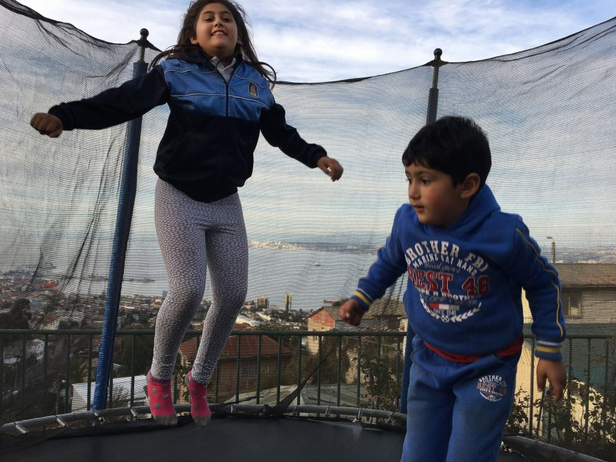 Westwater, Emma SIT Valparaiso Chile Spring 2018 My two host-cousins, Josefa and Alonso, jumping on the trampoline on their grandmother's patio after school on a Friday, which overlooks the city and port of Valparaíso.This photo was selected for the 2019 Barlow Off-Campus Photography Exhibition and shown at the 2019 Mount David Summit on March 29, 2019.